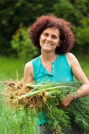 Young farmer woman holding a sheaf of dill freshly picked photo