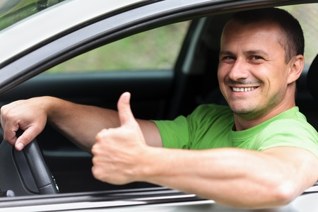 Happy young caucasian man at the wheel of his new car Stock Photo