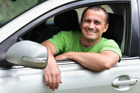 Happy young caucasian man at the wheel of his new car photo