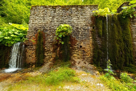 Landscape with an ancient stone wall and water flowing through it photo