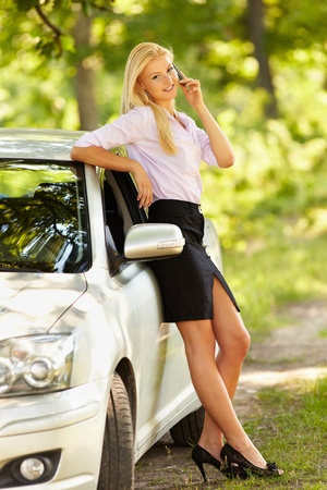 gorgeous businesswoman: Young businesswoman speaking on mobile phone, leaning against her new car
