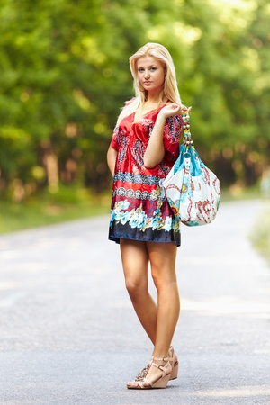 Full length portrait of a young blond woman in colorful dress with purse outdoor photo