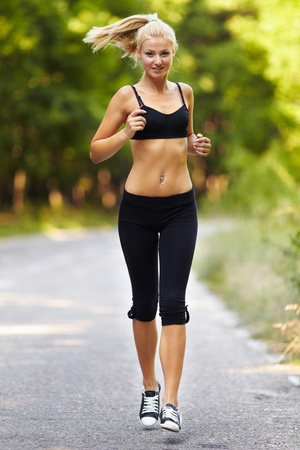 Young caucasian woman running through the forest, jogging photo
