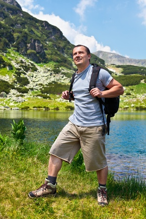 Portrait of a young mountaineer man with a backpack hiking into the mountains photo