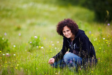 Portrait of a young attractive redhead woman with curly hair outdoor photo