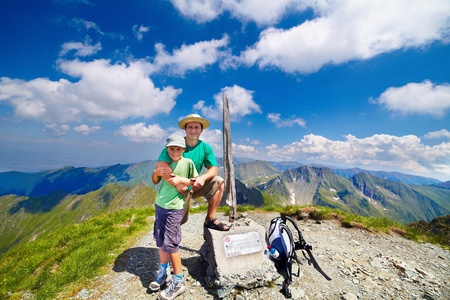 Happy father and son on the Buteanu peak in Romanian Carpathians, the inscriptions reads