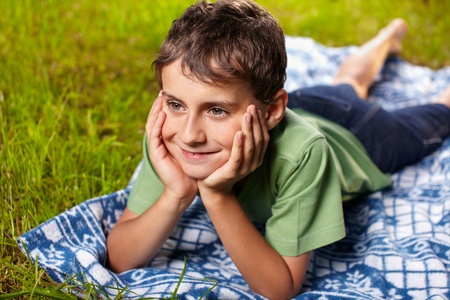 Closeup portrait of a happy boy smiling, lying on a blanket outdoor in the grass Stock Photo - 9999782