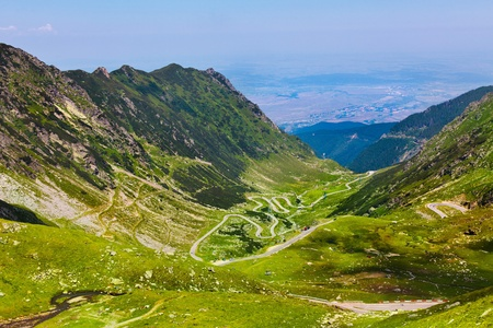 Landscape from the rocky Fagaras mountains in Romania in the summer with Transfagarasan winding road in the distance photo