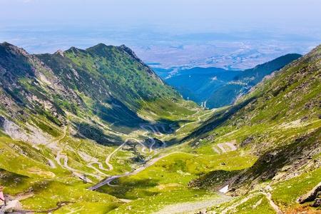 fagaras: Paesaggio dalla Montagne Rocciose Fagaras in Romania in estate con la strada tortuosa Transfagarasan in lontananza