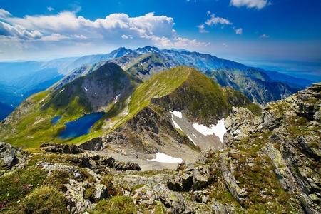 El paisaje de la Fagaras rocosas montañas en Rumania en el verano con lago Capra en la distancia