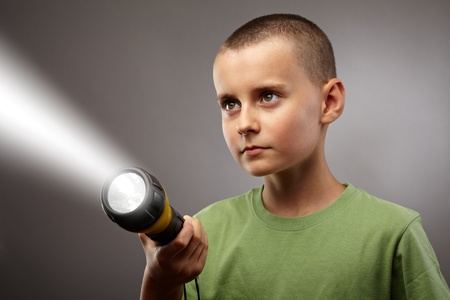 flashlights: Child with flashlight looking to find answers, studio concept shot