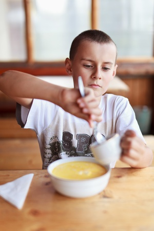 Boy eating soup for dinner in a rustic restaurant outdoor photo