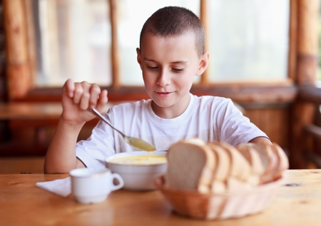 comiendo pan: Ni�o de comer sopa para la cena al aire libre en un restaurante r�stico