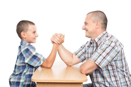 Father and son arm wrestling for fun, isolated on white background photo