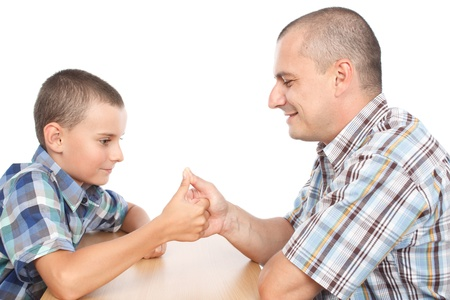 Father and son thumb wrestling for fun, isolated on white background photo