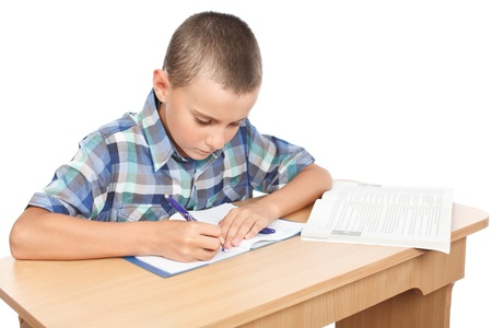 writing activity: Portrait of a school boy doing homework at his desk, isolated on white background