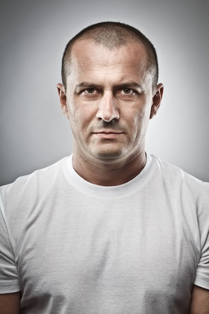 close up: Fine art portrait of a menacing man, studio close up Stock Photo
