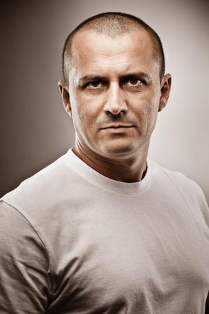 Fine art portrait of a menacing man, studio close up photo
