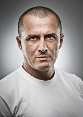 Fine art portrait of a menacing man, studio close up Stock Photo