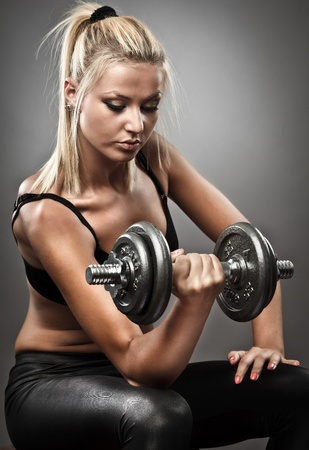 Young woman doing workout with weights, studio shot Stock Photo