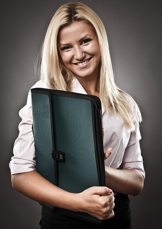 Studio portrait of an attractive woman holding a folder photo