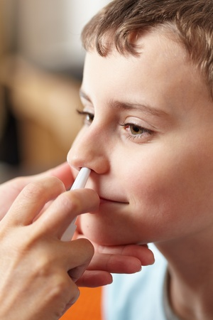 doses: Vrouw arts handen geven een jongen een dosis neusspray tegen griep Stockfoto