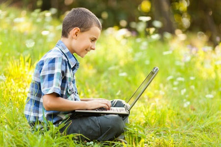 School boy using his laptop outdoor on a meadow photo