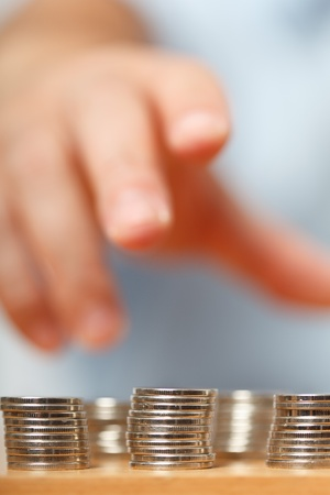 financial metaphor: Businessman reaching for pennies, financial crisis concept