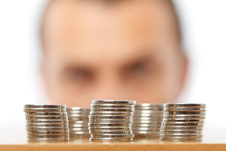 Businessman looking at piles of pennies, financial crisis or savings concept Stock Photo - 10497022