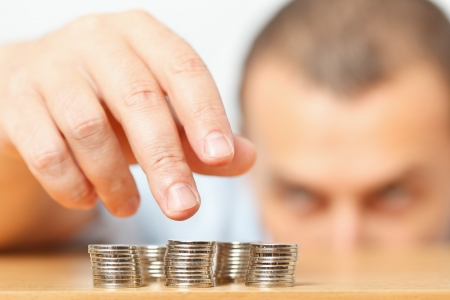 Businessman reaching for pennies, financial crisis or savings concept Stock Photo
