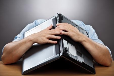 dolor de cabeza: Retrato de un empresario agotado que cubre su cabeza con su port�til