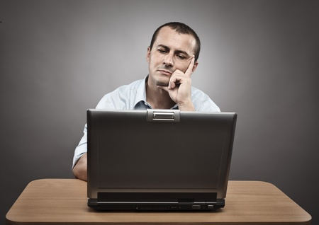 Studio portrait of a thoughtful businessman at his laptop Stock Photo - 10496984