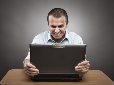yell: Portrait of an angry businessman at his laptop, on gray background