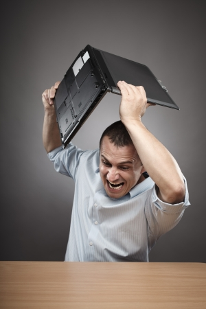 Extremely angry businessman smashing his laptop on the desk photo