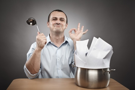 business metaphor: Concept image of a confident and successful businessman cooking contracts or paperwork