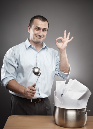 Concept image of a confident and successful businessman cooking contracts or paperwork photo