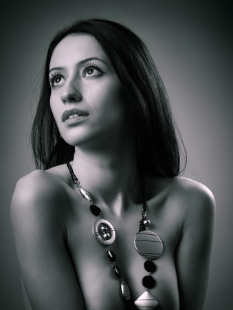 Monochrome glamour portrait of a beautiful nude woman with jewelry