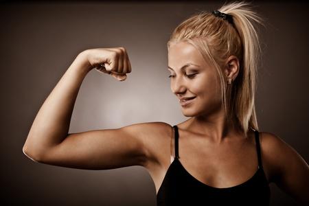 Athlétique jeune femme flexion ses biceps, studio abattu