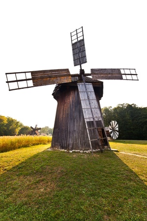 Ancient wind mill replica on a meadow at sunset photo