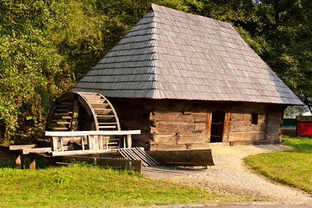 replica: Ancient wooden watermill replica in a meadow