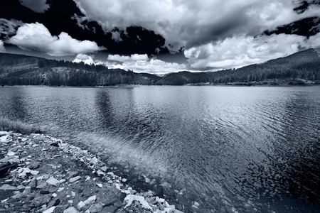 Monochrome toned landscape of a lake with dramatic sky photo