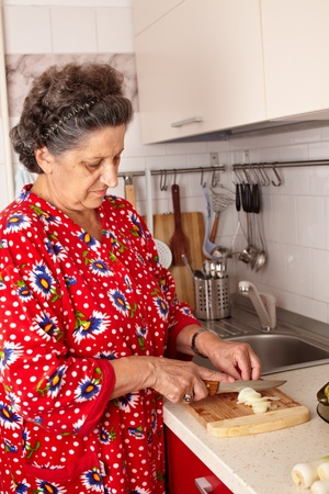 Caucasian senior woman in the kitchen with vegetables, preparing meal Stock Photo