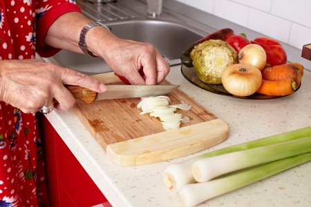 Senior woman hands chopping vegetables on a wooden board in the kitchen Stock Photo - 10930149