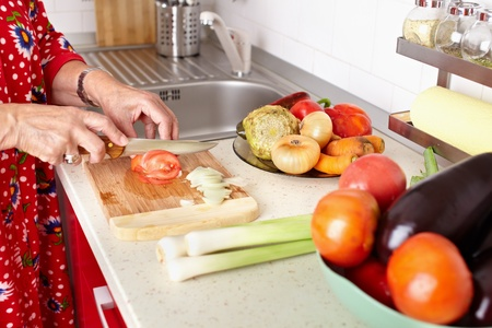 Senior woman hands chopping vegetables on a wooden board in the kitchen Stock Photo - 10930135
