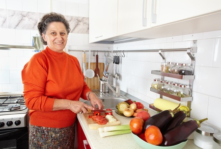 Caucasian senior woman in the kitchen with vegetables, preparing meal photo