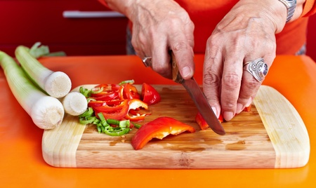 Senior woman hands chopping vegetables on a wooden board in the kitchen Stock Photo - 10929960