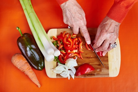 Senior woman hands chopping vegetables on a wooden board in the kitchen Stock Photo - 10930120