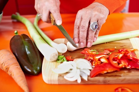 Senior woman hands chopping vegetables on a wooden board in the kitchen Stock Photo - 10929981