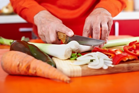Senior woman hands chopping vegetables on a wooden board in the kitchen Stock Photo - 10929977