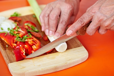 Senior woman hands chopping vegetables on a wooden board in the kitchen Stock Photo - 10930144